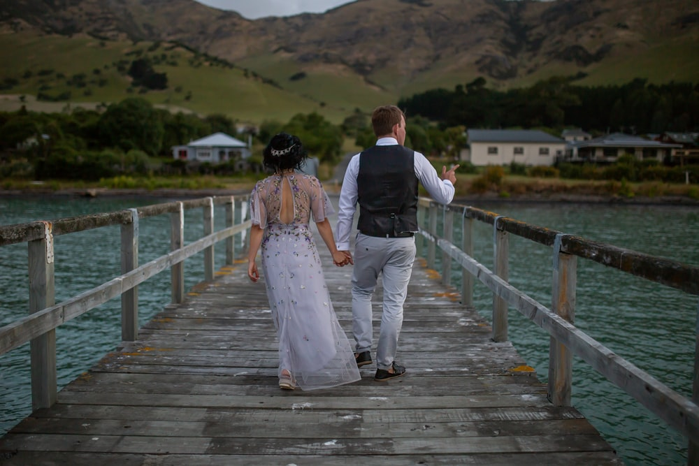 man and woman walking on wooden dock during daytime