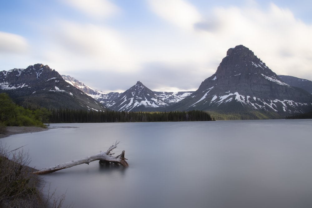 brown wooden boat on lake near snow covered mountain during daytime