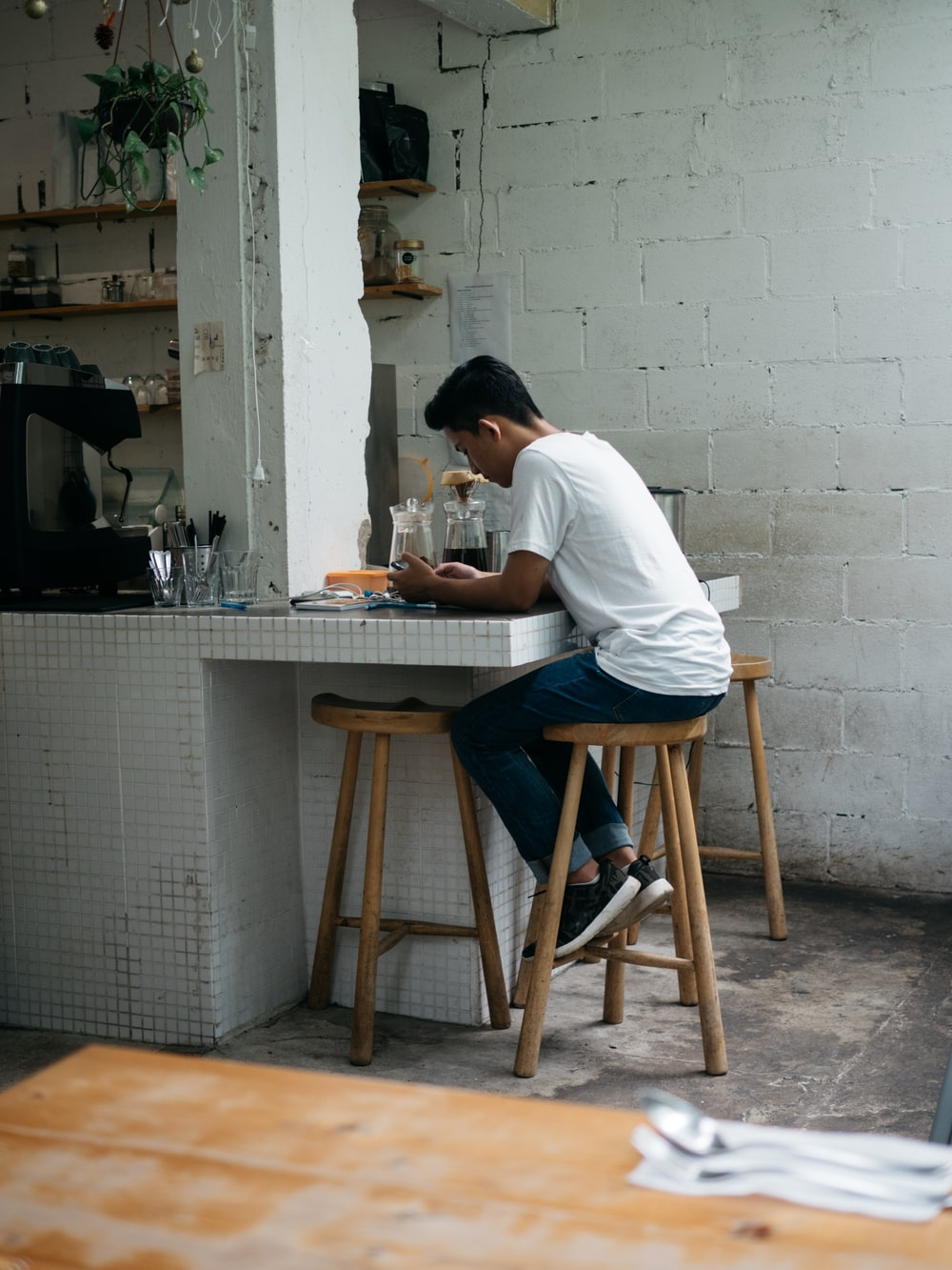 man in white shirt sitting on brown wooden chair