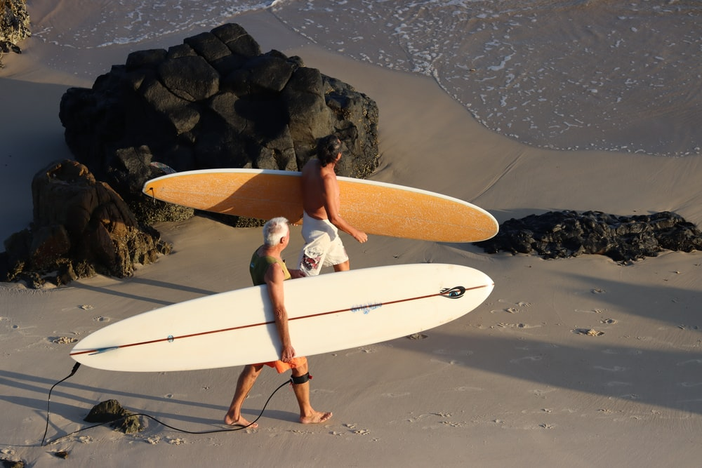 man in blue shorts holding white surfboard on beach during daytime