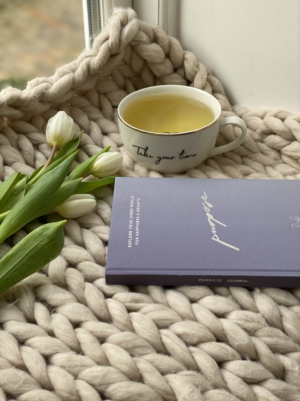 black book beside white ceramic mug on white knit textile