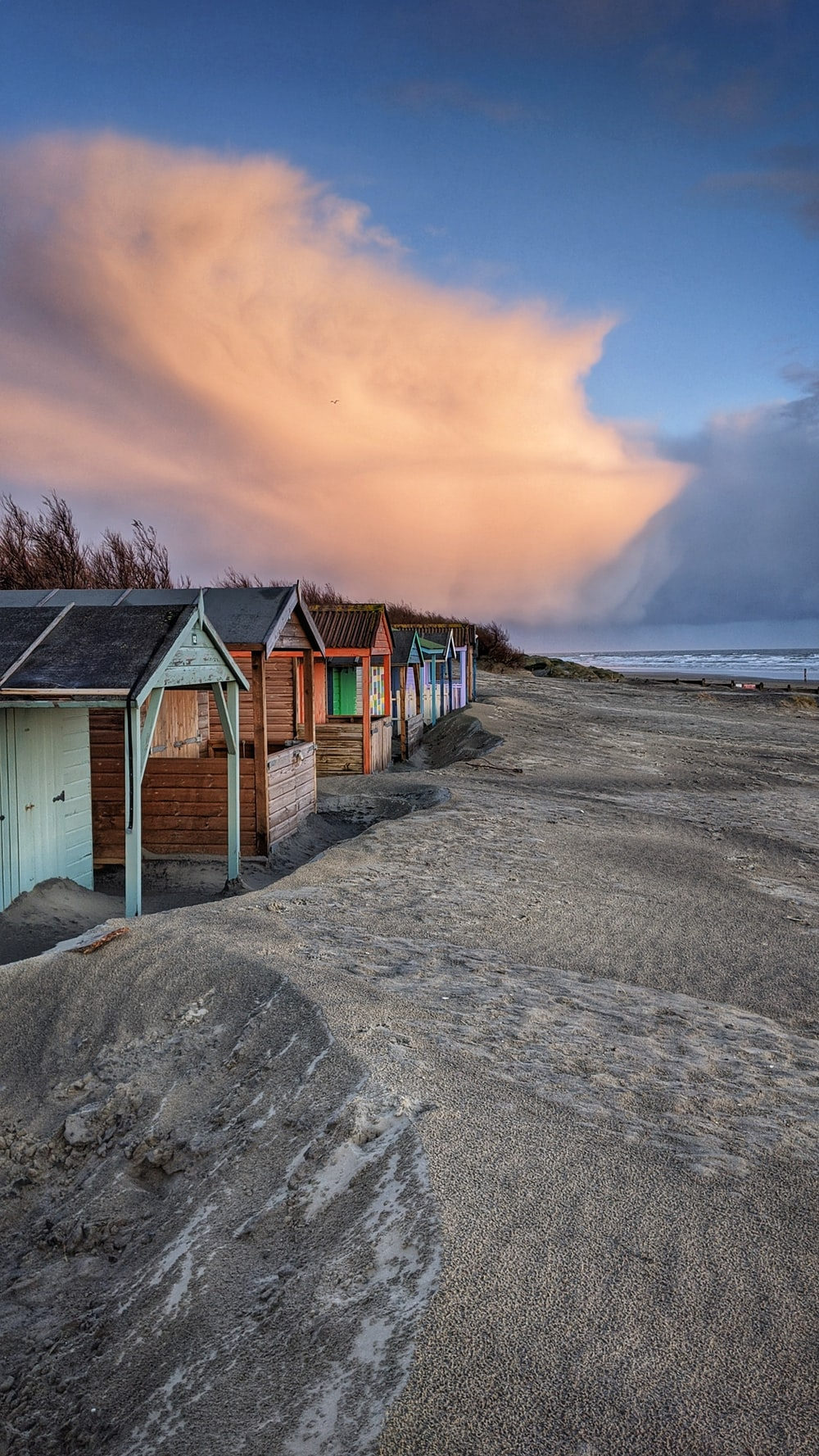 brown wooden houses on gray sand near body of water during sunset