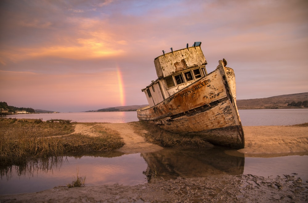 brown ship on sea shore during sunset