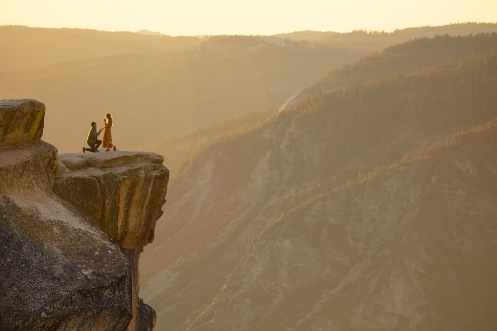 person sitting on rock formation during daytime