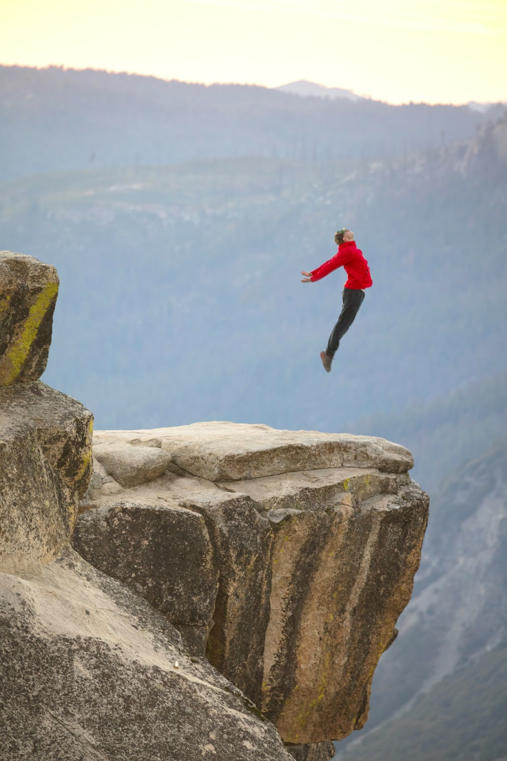 man in red long sleeve shirt and black pants jumping on brown rock during daytime
