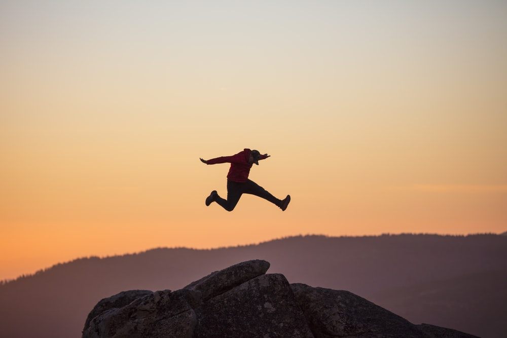 man jumping on rocky mountain during daytime