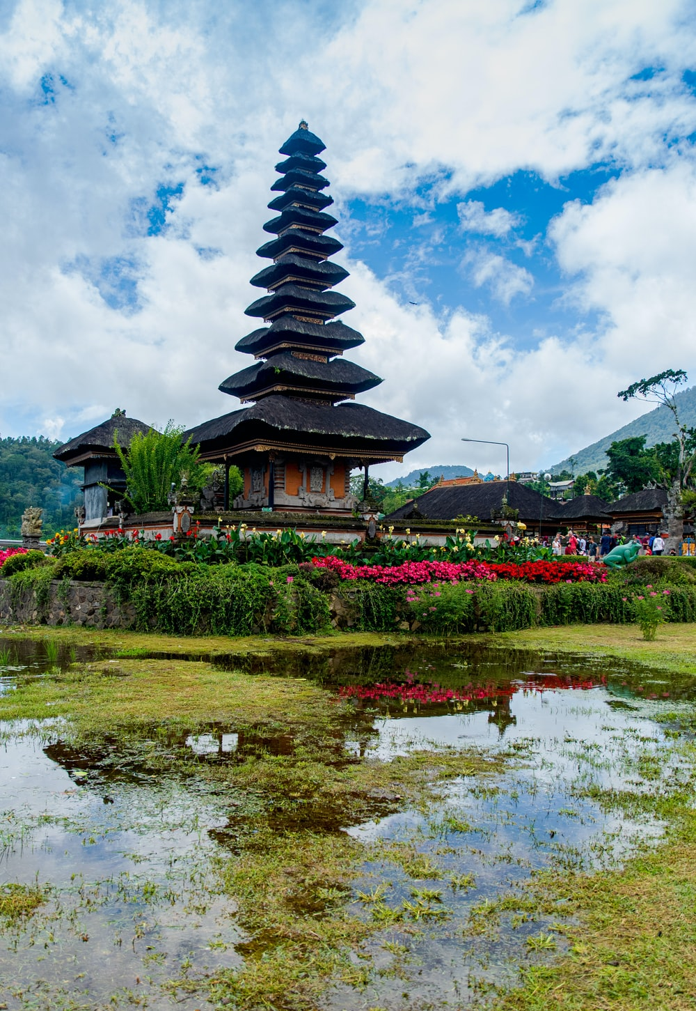 black and white pagoda temple near green grass field under blue and white cloudy sky during