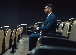 man in blue dress shirt sitting on black chair