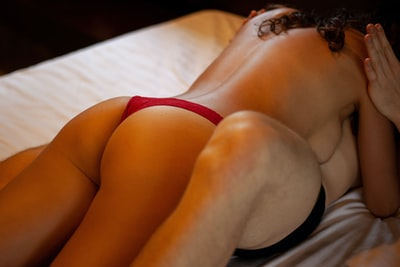 A nude model laying on top of a man in the bed. Erotic, suggestive photo.