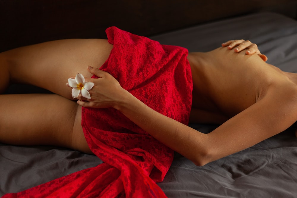 woman in red dress lying on bed