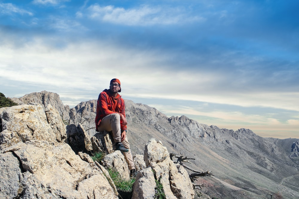 man in red jacket sitting on rock formation during daytime