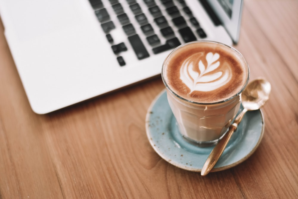 white ceramic cup on saucer beside macbook pro