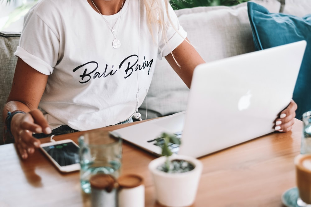 woman in white crew neck t-shirt sitting by the table with macbook