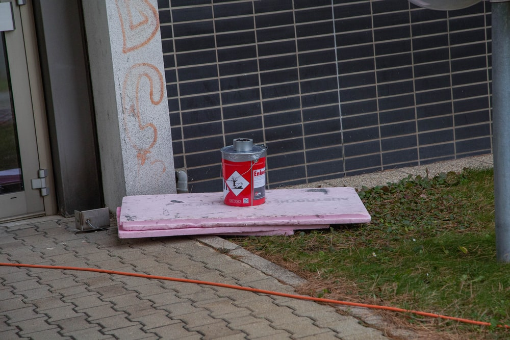 coca cola can on pink and white concrete bench