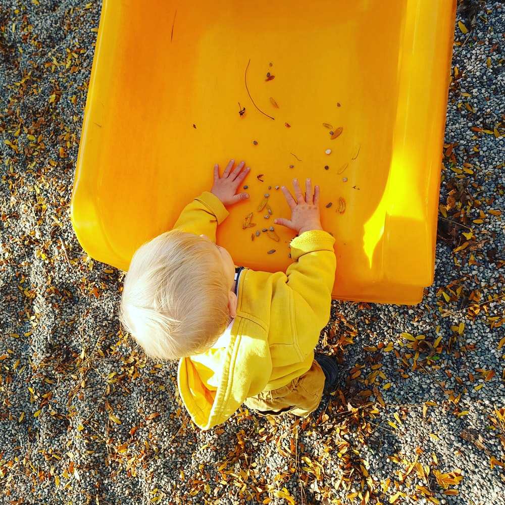 child in yellow long sleeve shirt and pants playing on yellow plastic container