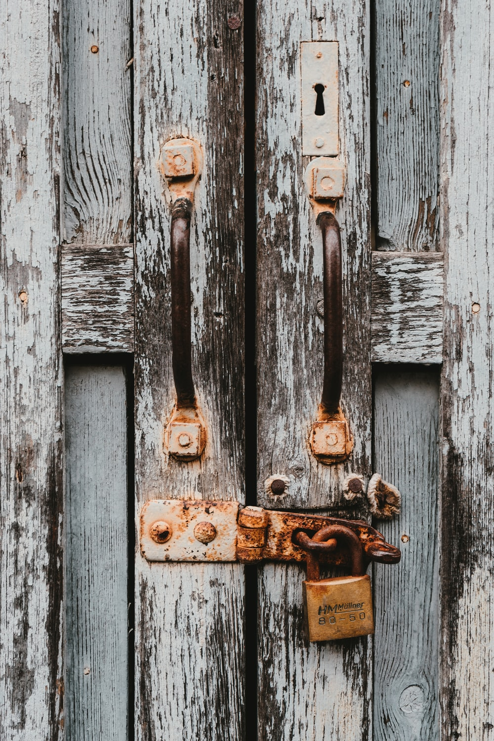 white and brown wooden door with padlock