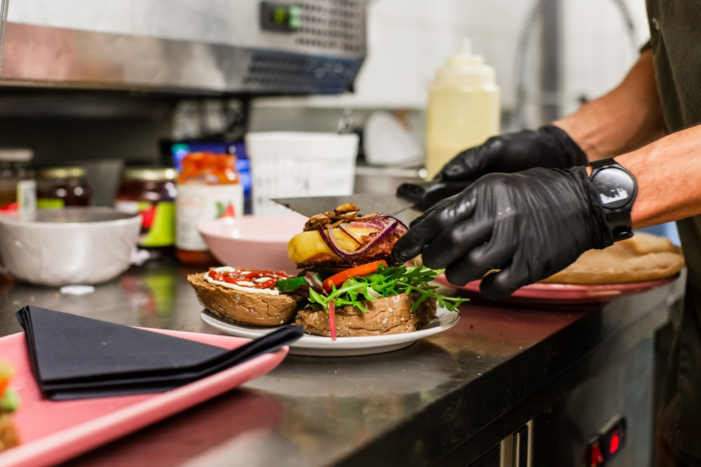 person in black leather jacket holding burger
