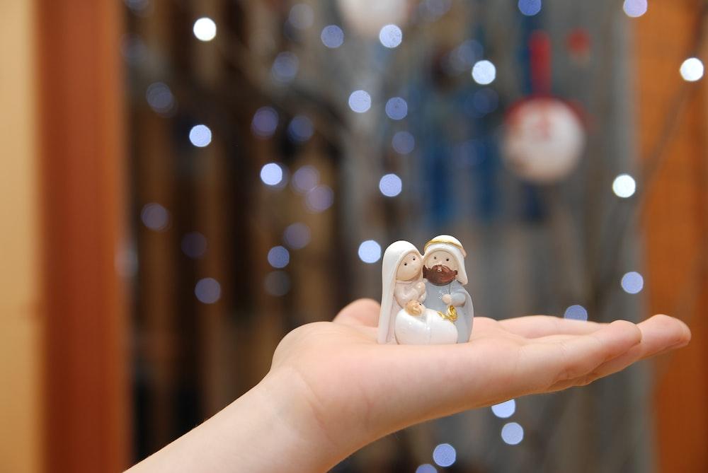 person holding white ceramic figurine