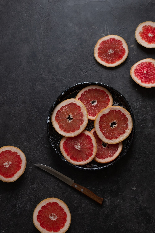 sliced orange fruit on black round plate