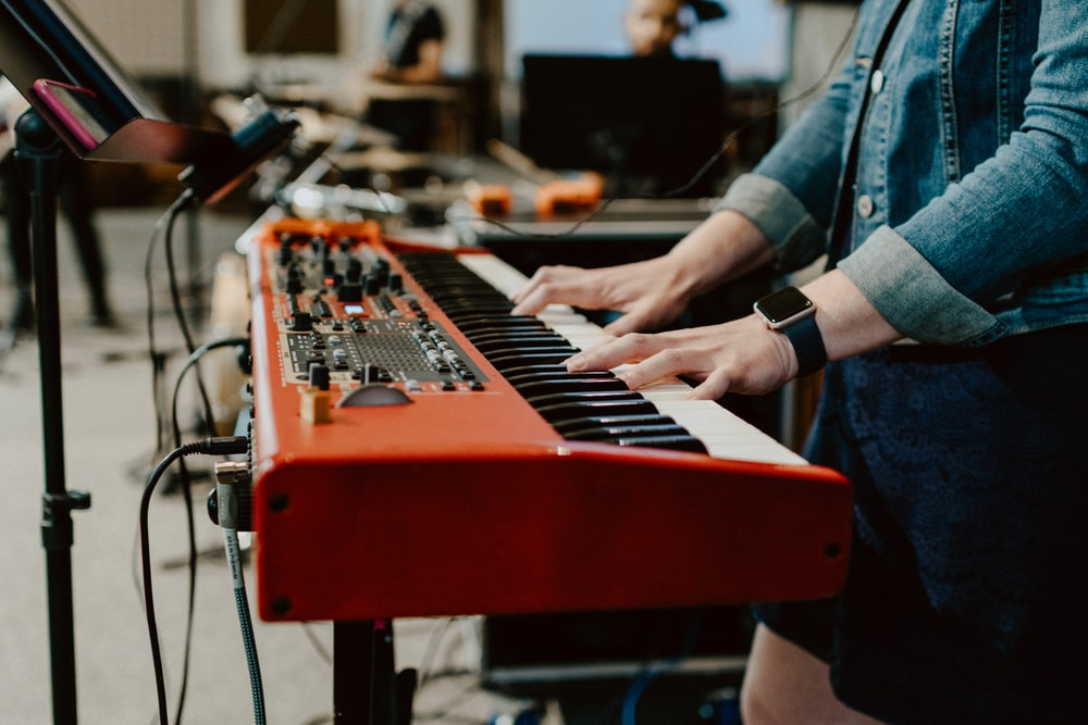 person playing red and black electric piano