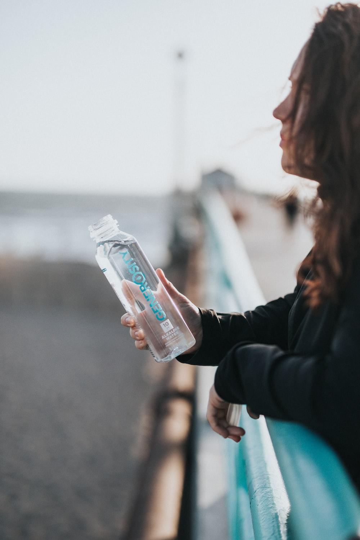 woman in black long sleeve shirt holding white plastic bottle