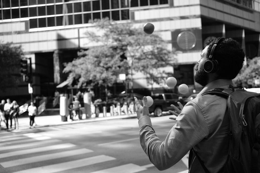 丸いボールを保持しているパーカーの人のグレースケール写真