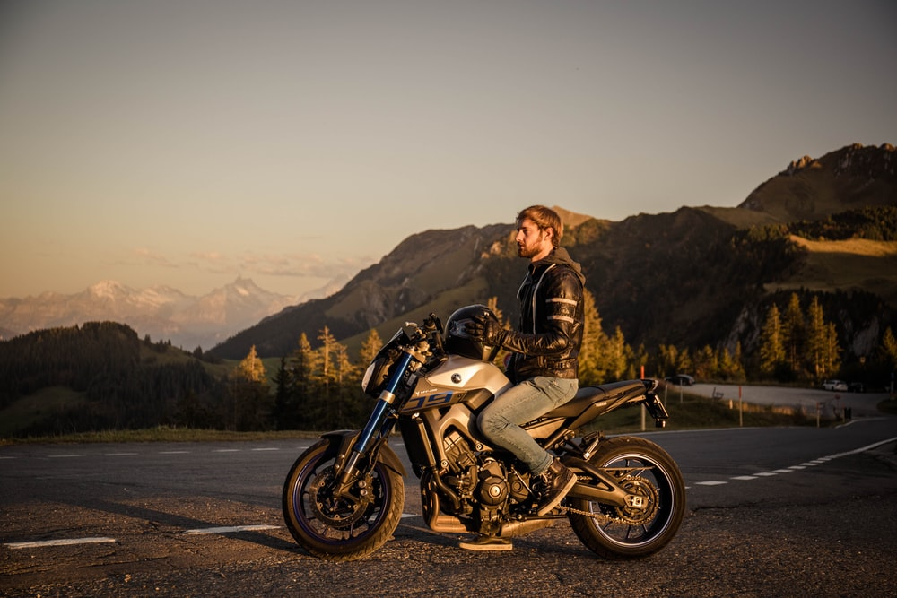 man in brown jacket riding on white and black motorcycle