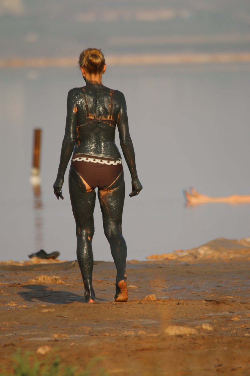 woman in black leather jacket and black pants standing on brown sand during daytime