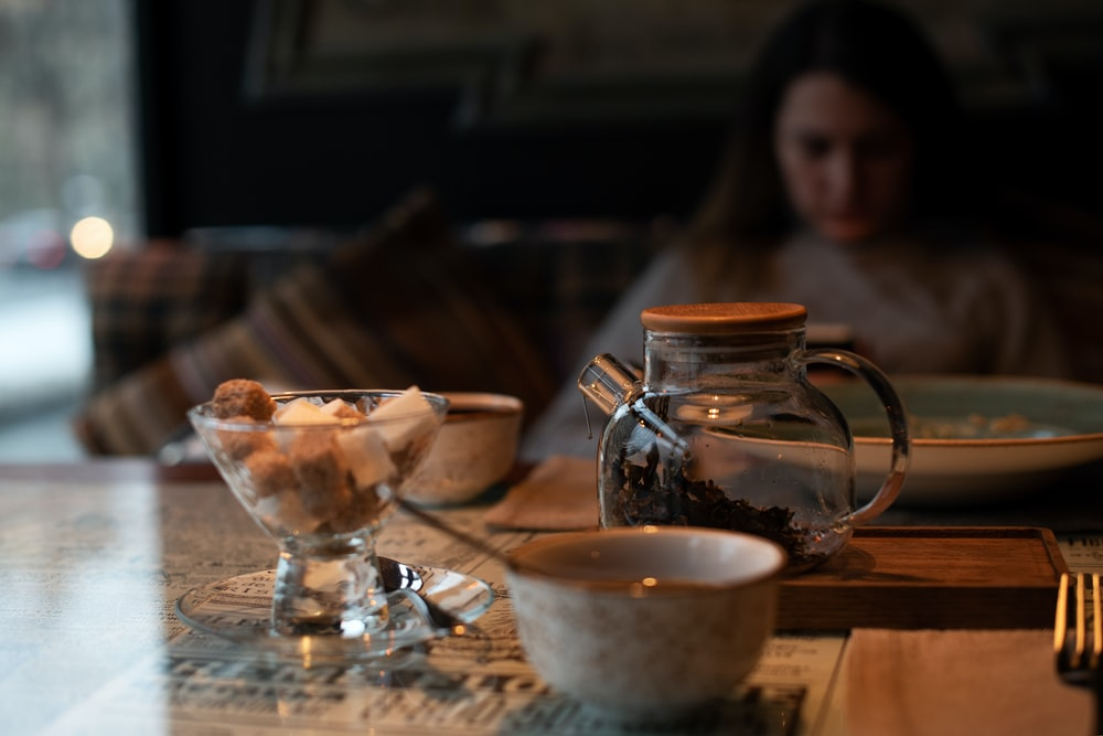 woman in black shirt sitting beside table with white ceramic bowl and clear glass pitcher