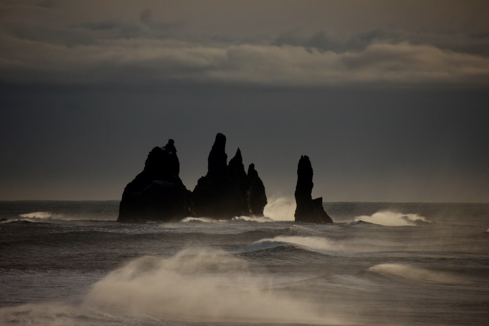 silhouette of rock formation on sea under gray clouds