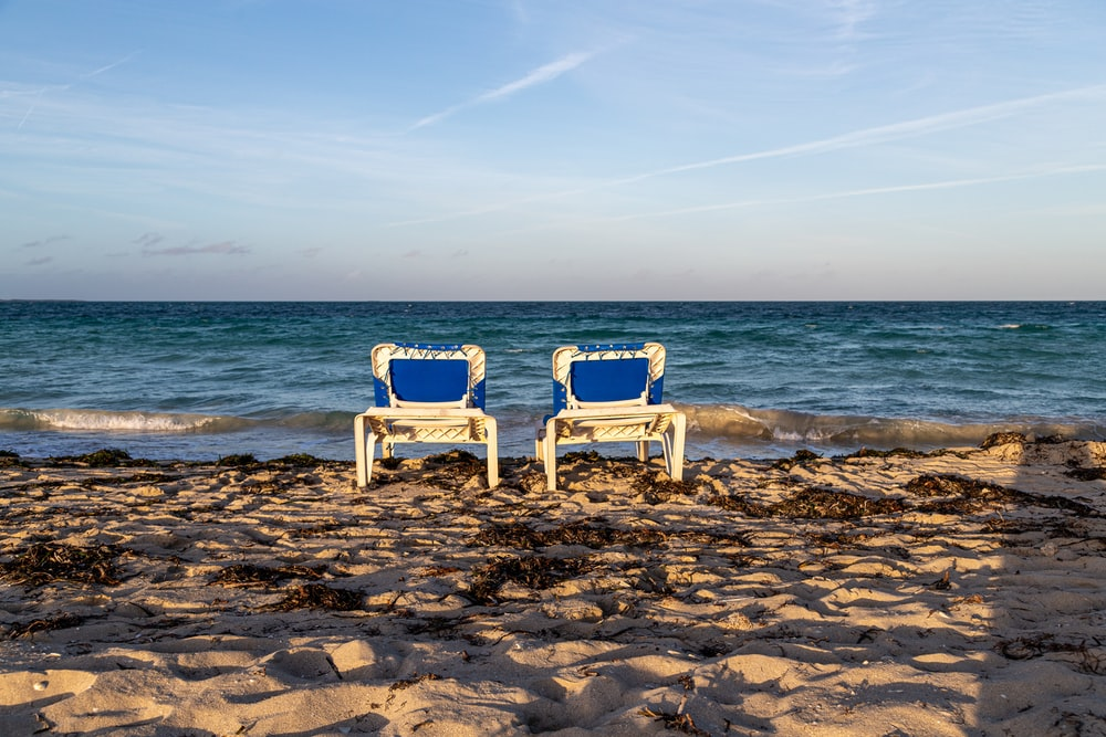 white wooden armchair on beach shore during daytime