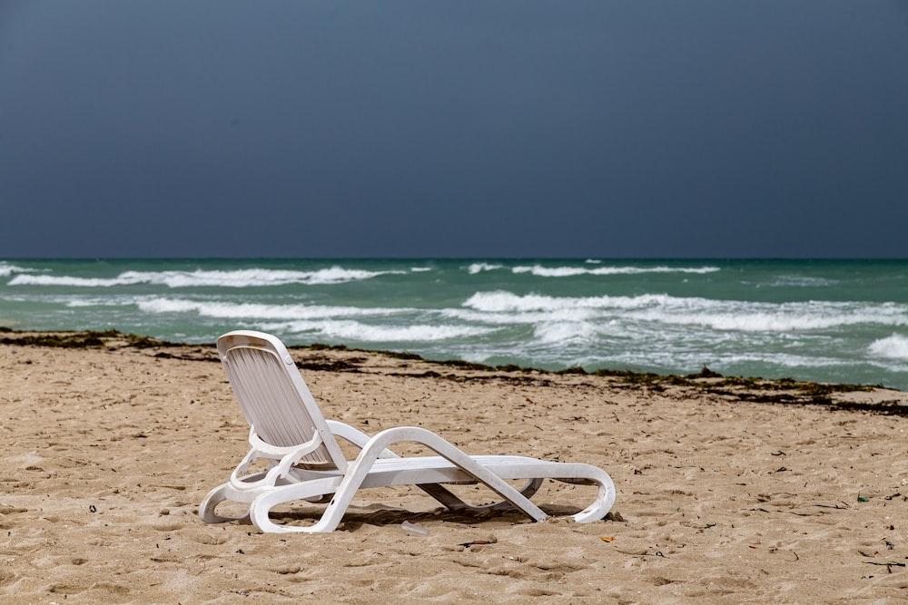 white plastic armchair on beach shore during daytime