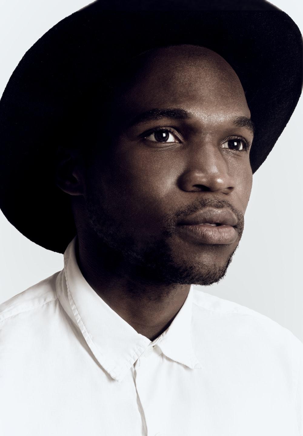 man in white dress shirt wearing black hat