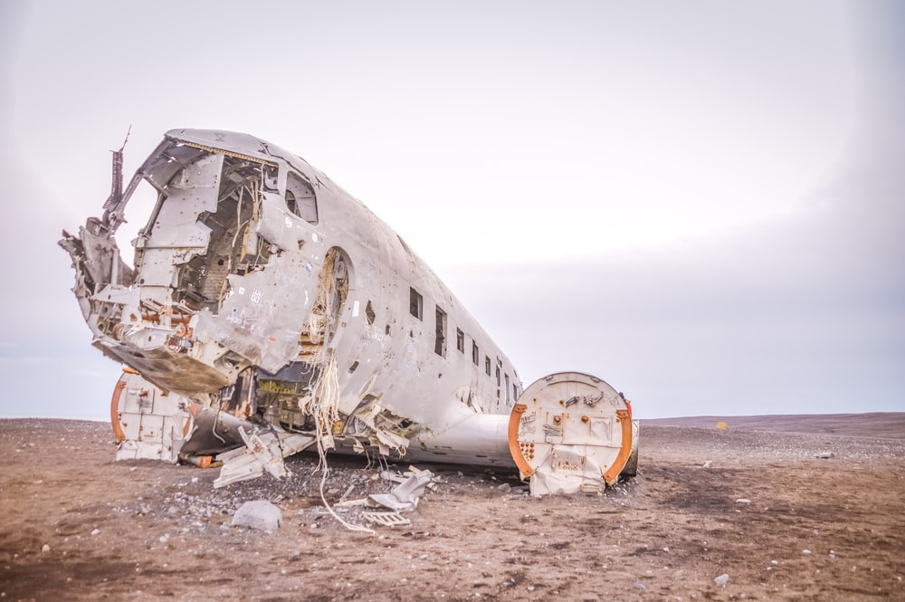wrecked airplane on brown sand during daytime