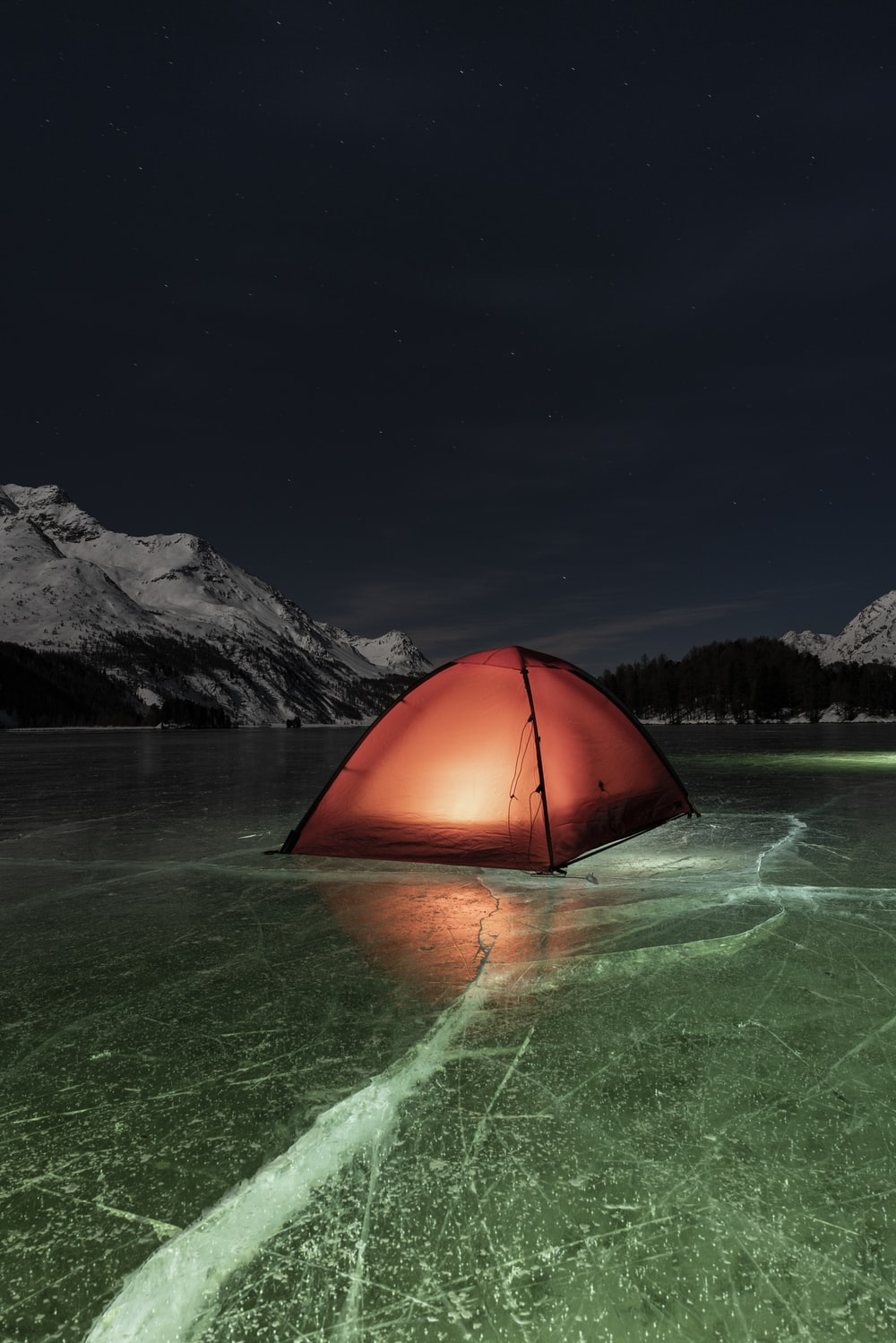 orange dome tent on green water near mountain during night time