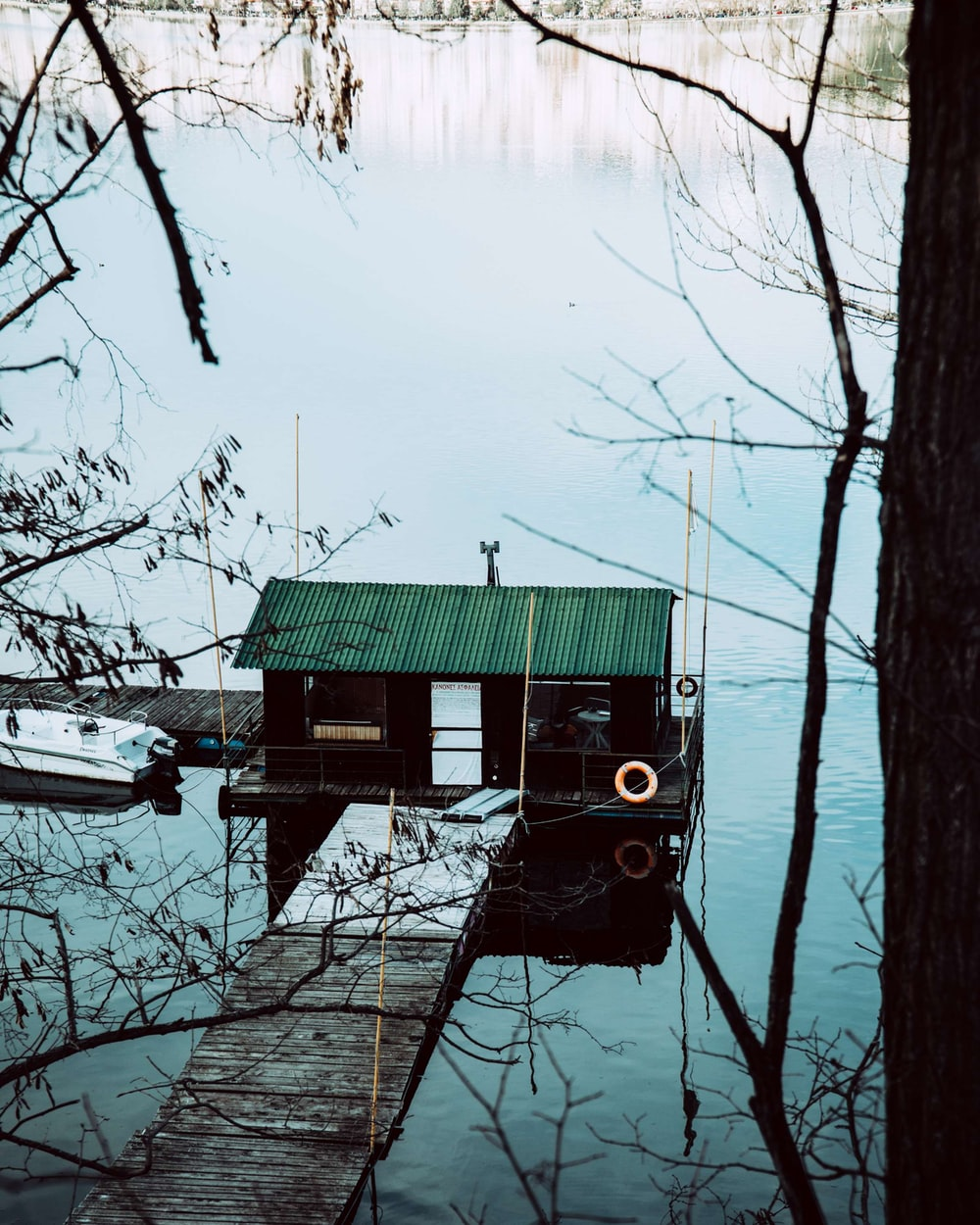 green wooden house on lake during daytime