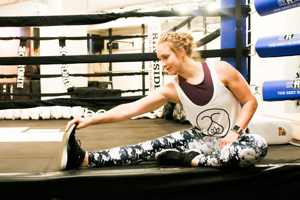 woman in white tank top and black and white pants sitting on black bench