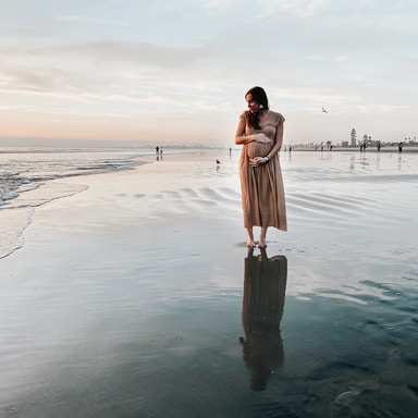 woman in brown dress standing on beach during daytime