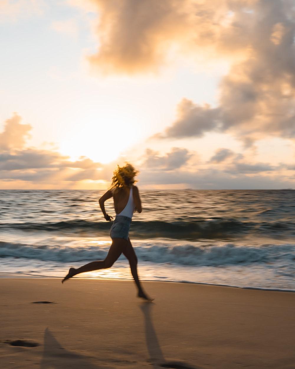 woman in white bikini standing on beach during sunset