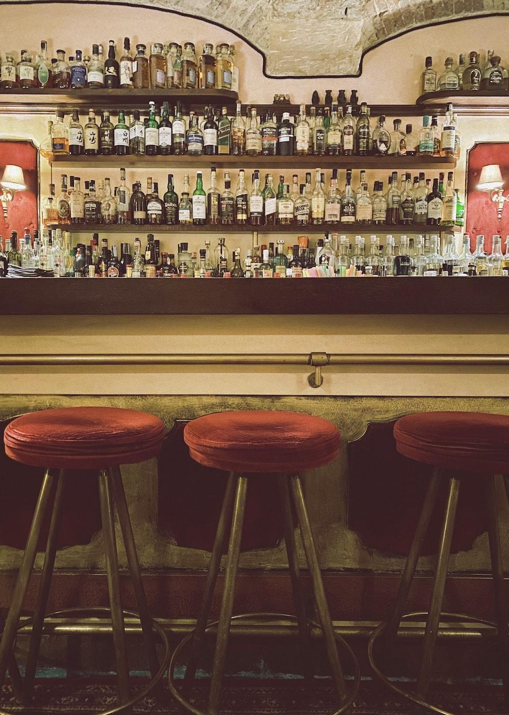 brown wooden bar stools beside bar counter