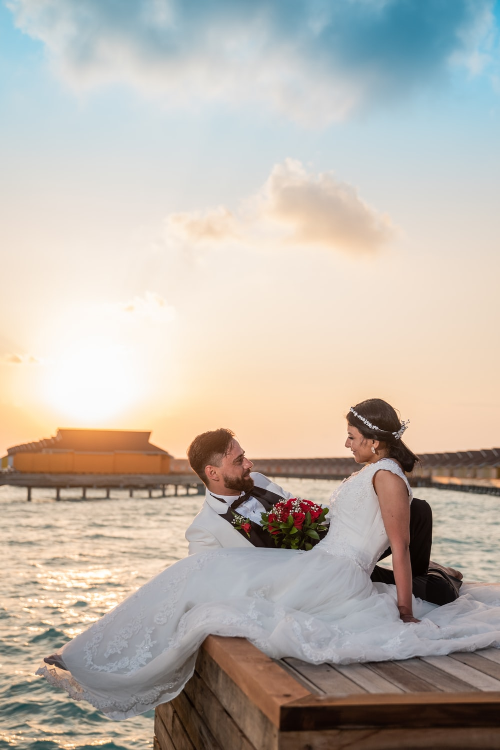 man in white suit kissing woman in white wedding dress