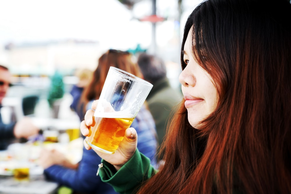 woman in green long sleeve shirt holding drinking glass with yellow liquid