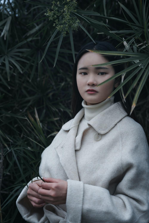 girl in beige coat standing near green plant