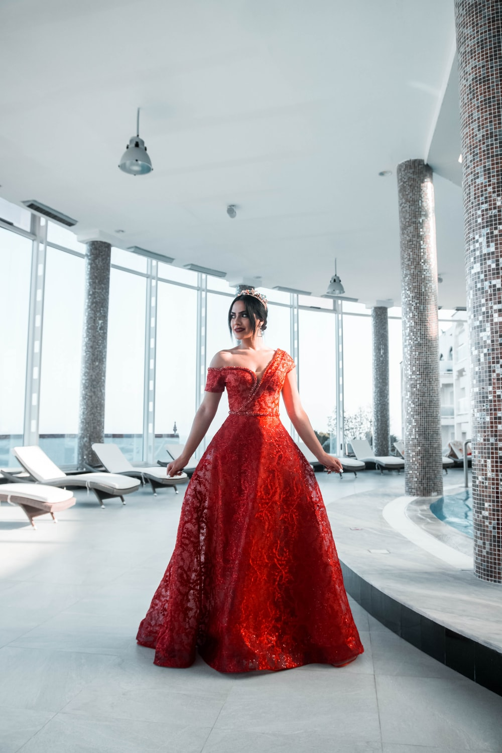 woman in red sleeveless dress standing on white floor