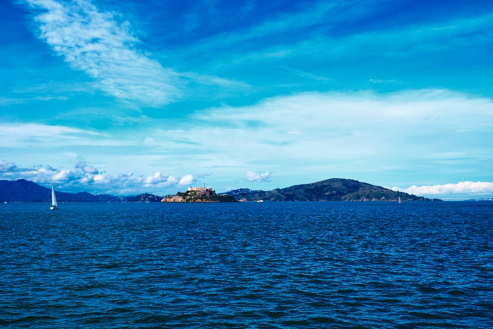 blue sea under blue sky and white clouds during daytime