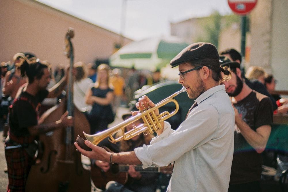 man in white thobe playing trumpet during daytime