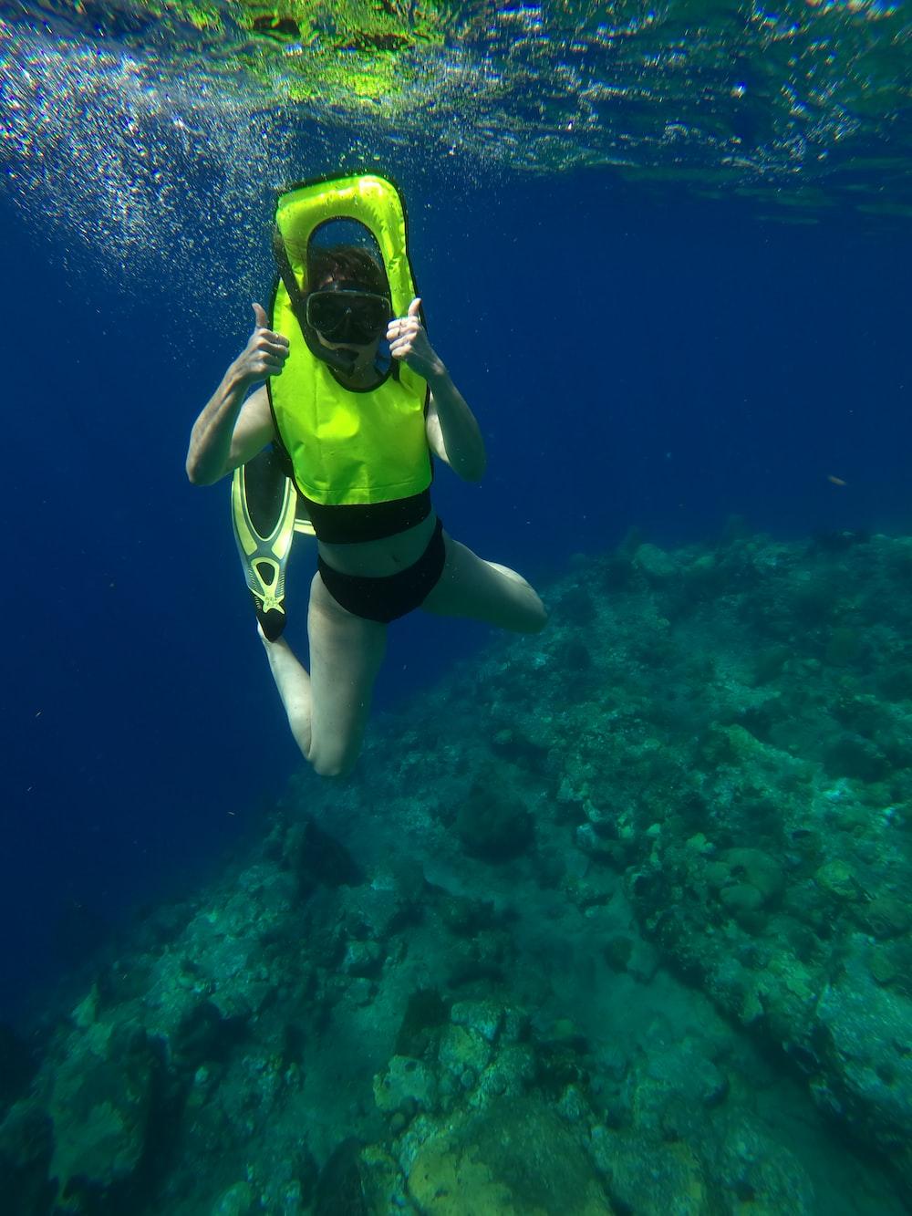 woman in yellow and black bikini swimming in the sea