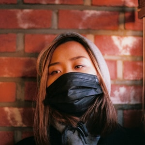 woman in black leather jacket covering face with black scarf