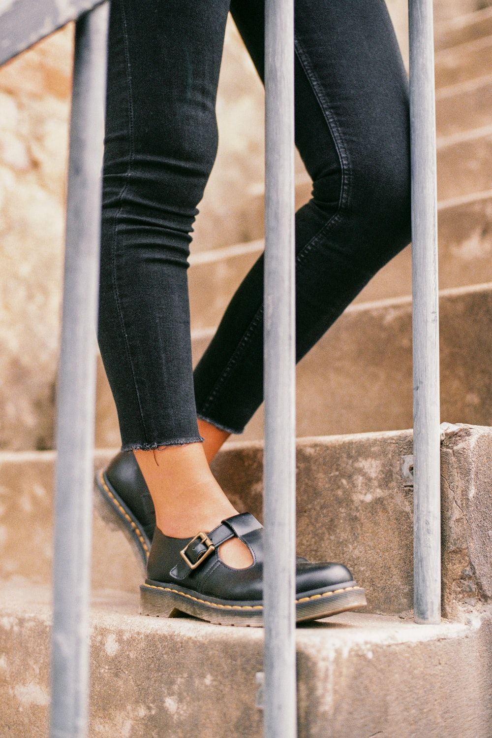 person wearing blue denim jeans and black leather peep toe sandals