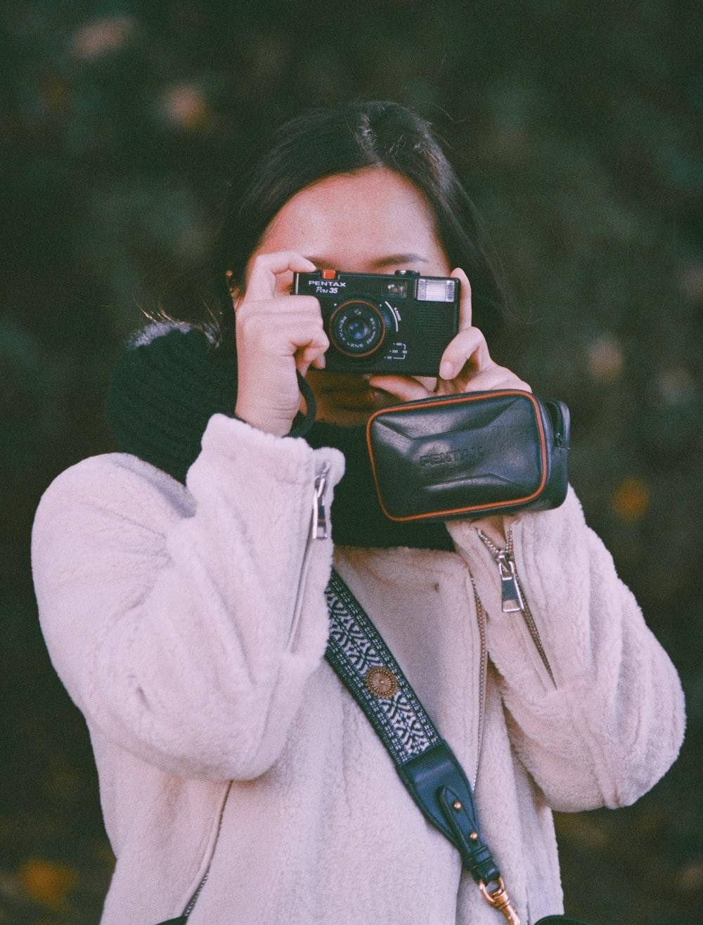 woman in white coat holding black dslr camera